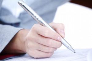 close up of person signing document with pen: Lawtery X Wills and Estate Planning Blog