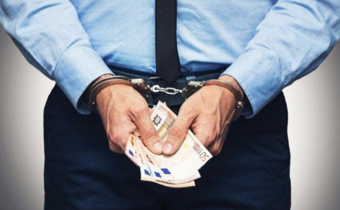 man in handcuffs holding money indicating guilty of corruption