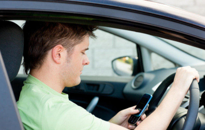 Man driving while using mobile: LawteryX Current News and Events Blog