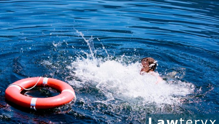 A man splashing in water near a life buoy
