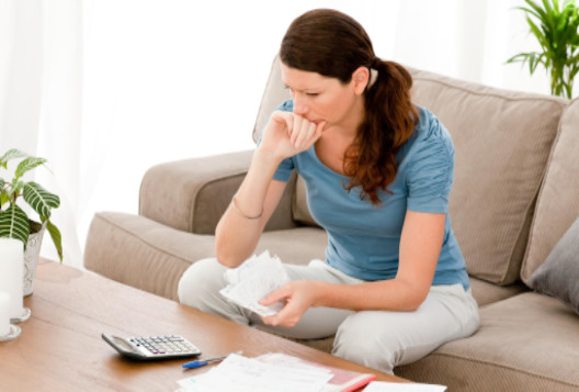 Anxious woman looking at finances: LawteryX Bankruptcy Blog