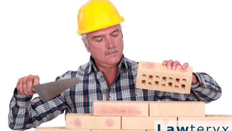 older construction worker laying bricks