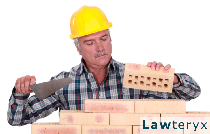 older construction worker laying bricks