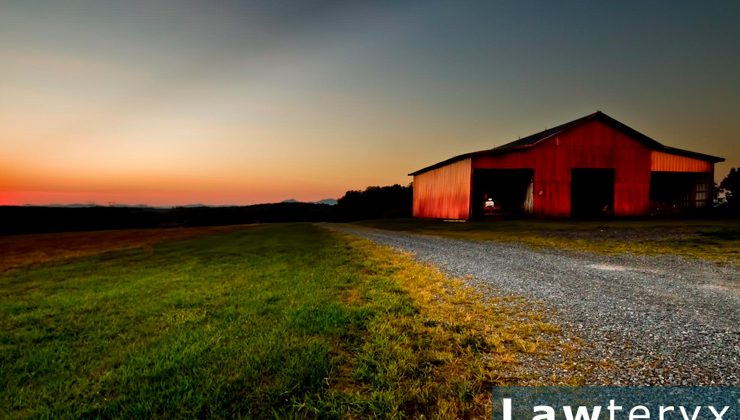 red barn sitting on farmland at sunset