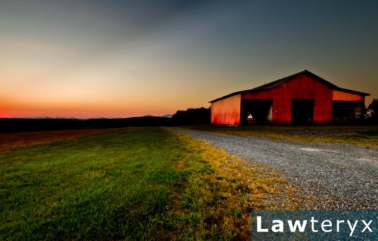 red barn sitting on farmland at sunset
