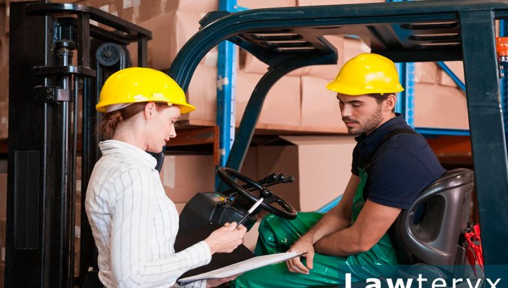 A warehouse employee sits on a forklift while discussing workplace injury and illness rules with another employee